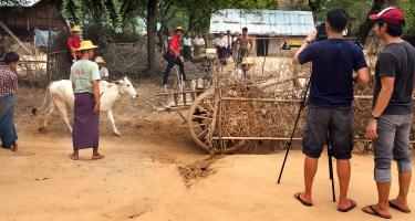 Man taking photo of wooden cart with people and cow around