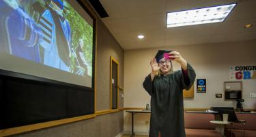 Lexy Greenwell waves at President Kington through the phone, President on screen in background
