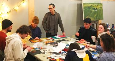 Participants work on their projects around a common table