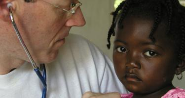 Dr. Farmer listening to young girls chest with stethescope