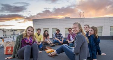 Smiling students from Opera, Politics, and Society in Modern Europe course sitting in a relaxed circle on a rooftop, with sun setting in the distance