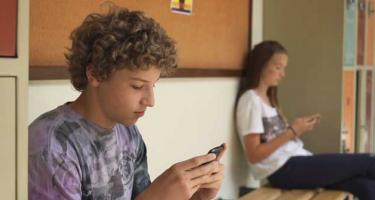two teenagers sitting on a wooden bench between lockers gaze at their mobile phones