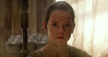 Rey in a room, brightly lit curtains behind her.