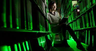 Emily Mesev '15, lit in green, between library stacks