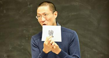 Professor holds up card with character
