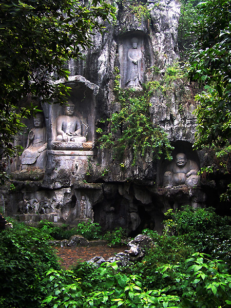 Statues carved into large, vine covered rock