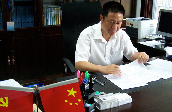Man working at his desk with small Chinese and Russian flags in foreground.