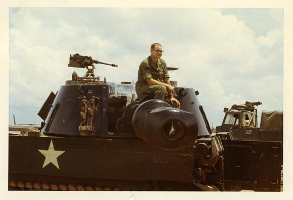 Holbrook sitting on howitzer
