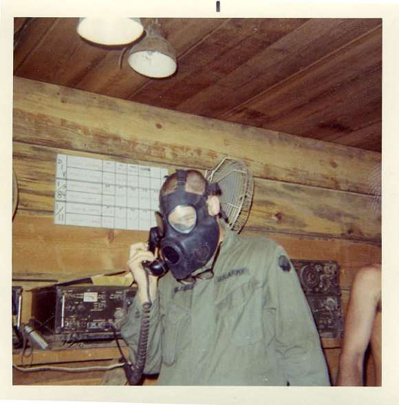 Man in gas mask talking into a mouthpiece
