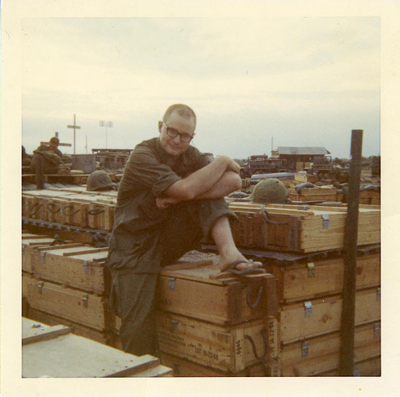 Holbrook in sandals sitting on wooden boxes, crosses in background