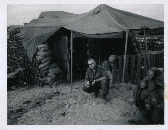 Holbrook crouched in front of a crude tent