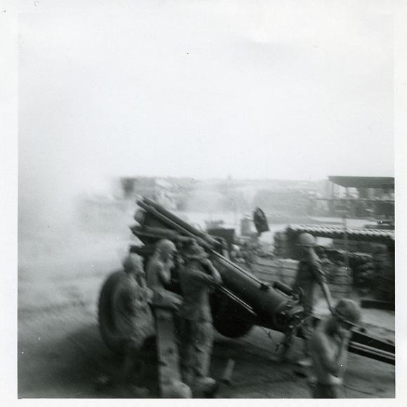 Men plugging their ears as an artillery gun goes off