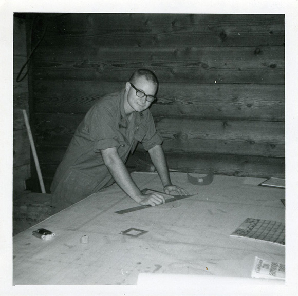 Holbrook leaning over charts with ruler in hand