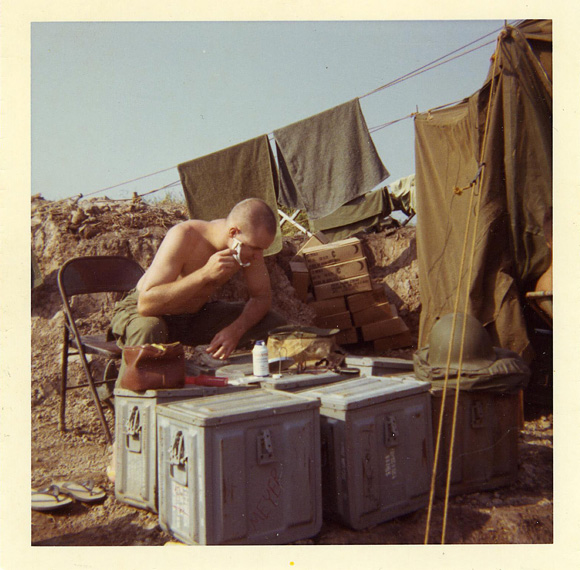 Man shaving in the open with gear on ammo boxes and clothes and towels drying behind him