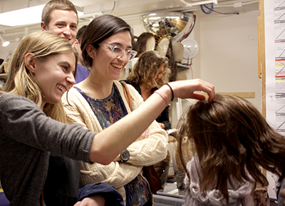Students taking a close look at a wig in a room full of other wigs